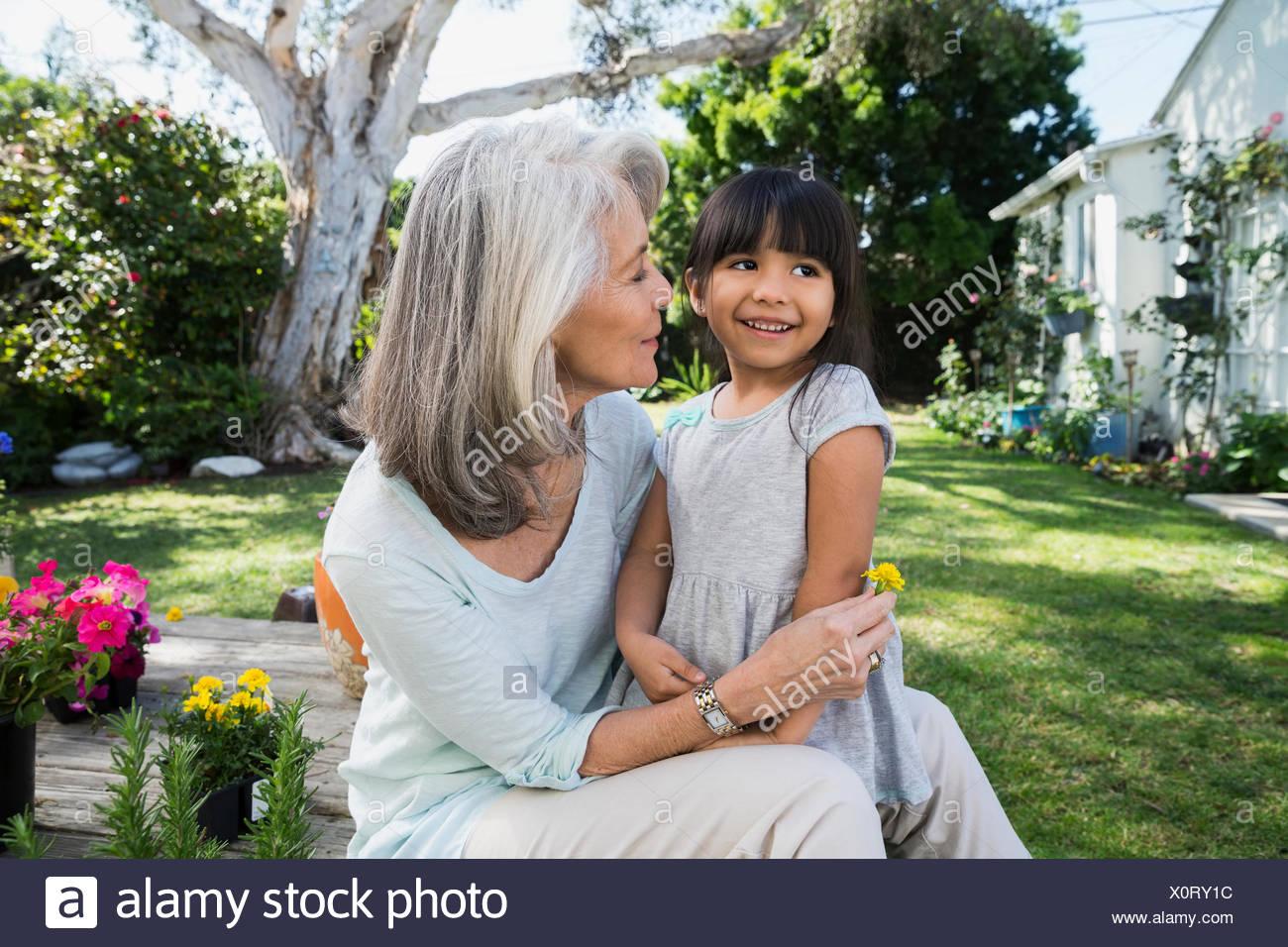 Granddaughter and grandmother hugging in backyard garden - Stock Image