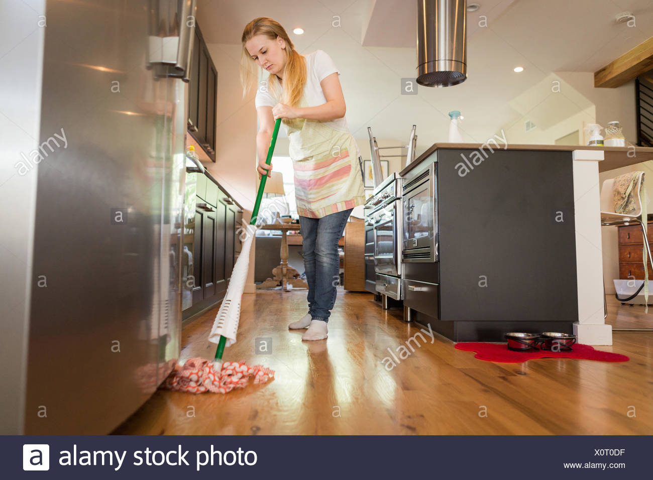 Young woman mopping with green cleaning products - Stock Image