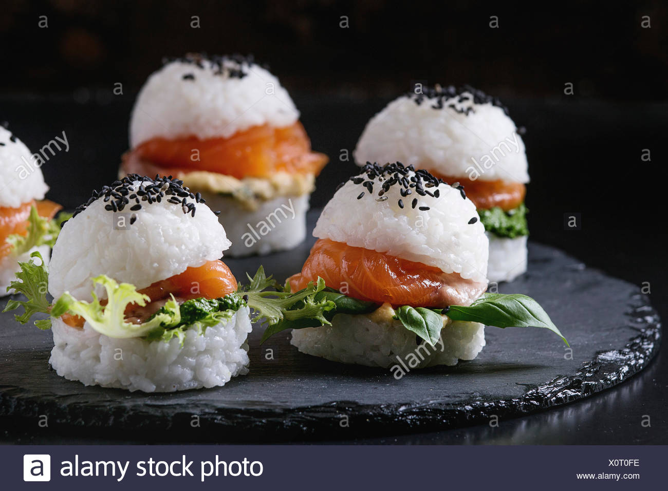 Mini rice sushi burgers with smoked salmon, green salad and sauces, black sesame served on slate stone board over black background. Modern healthy foo - Stock Image