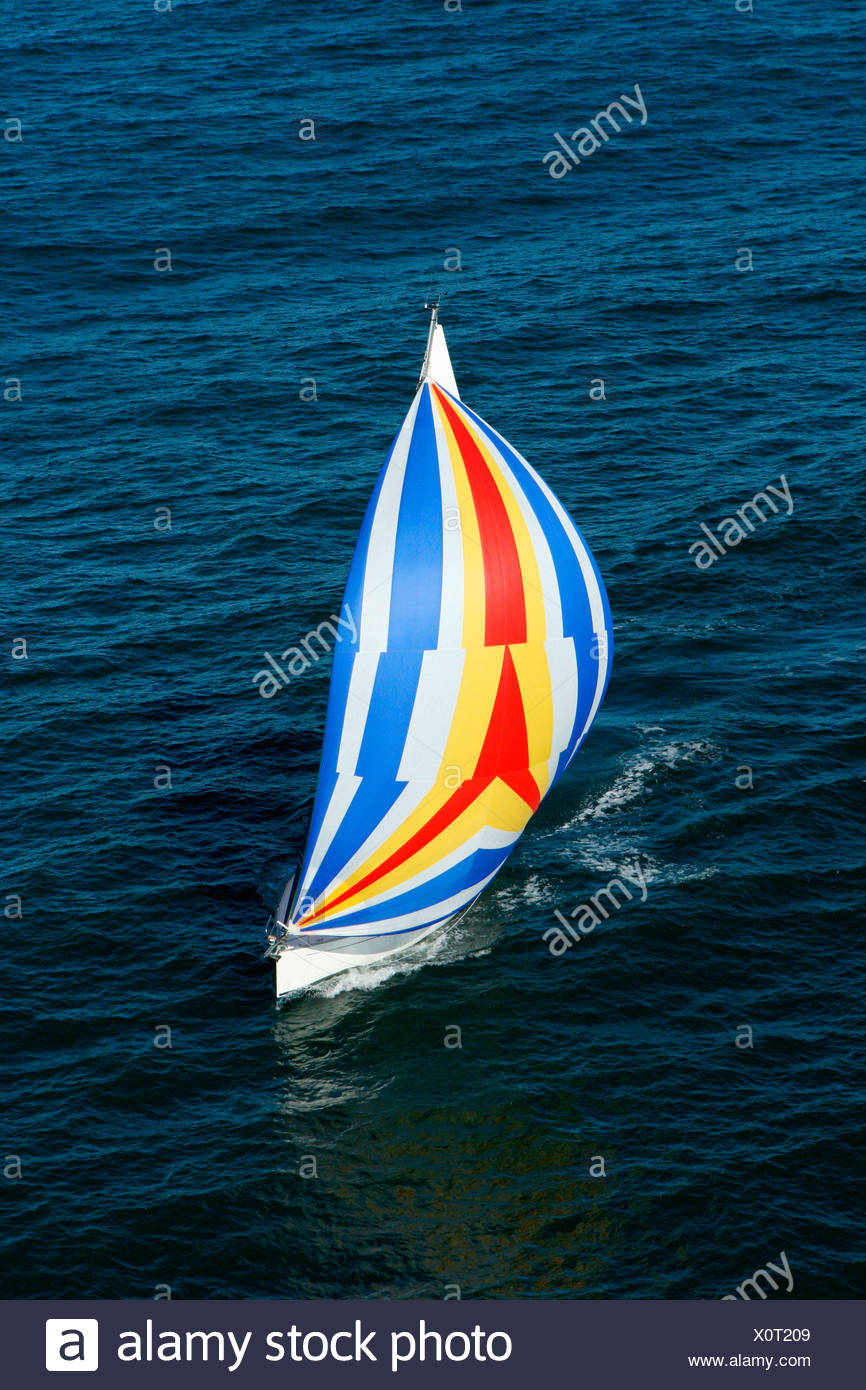 Aerial view of a sailing yacht with a colorful spinnaker cruising in Pittwater on the North Shore from Sydney, Australia. - Stock Image