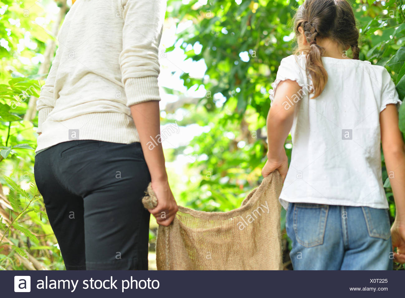 Rear view of woman and girl carrying burlap sack through garden - Stock Image