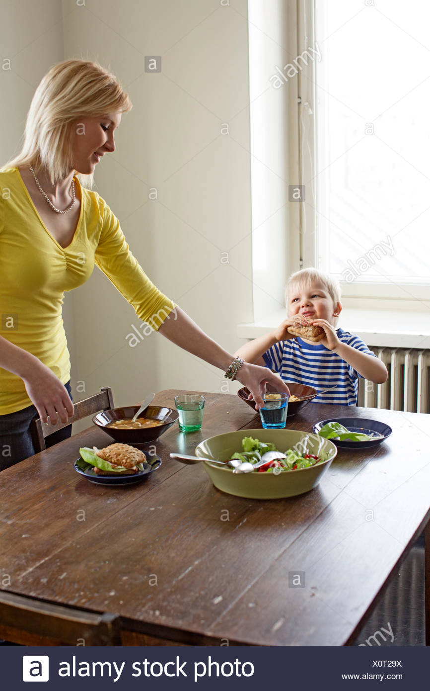 Finland, Helsinki, Kallio, Mother putting a glass of water before son at lunch table - Stock Image
