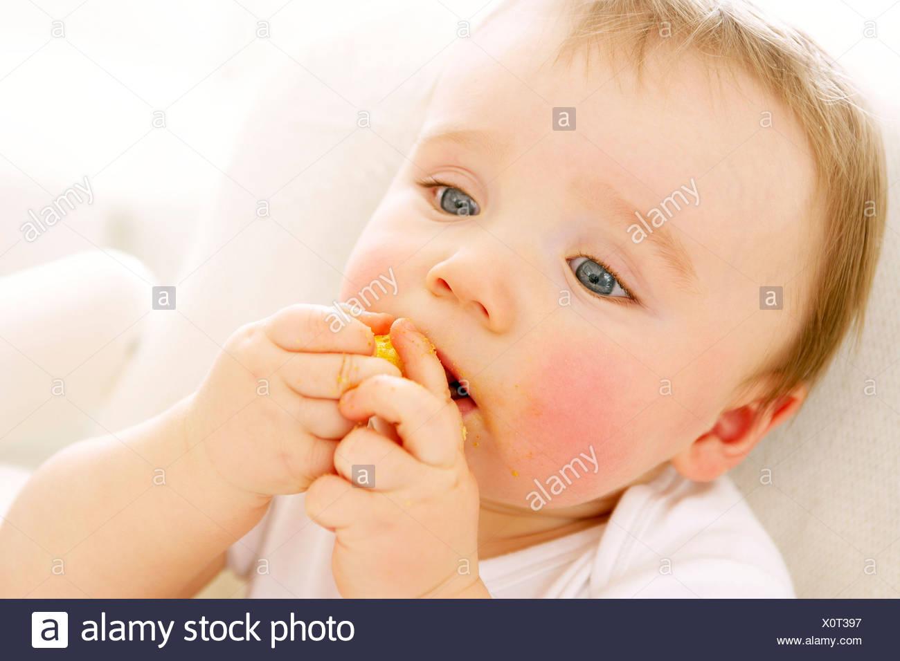 Baby boy eating a crisp - Stock Image