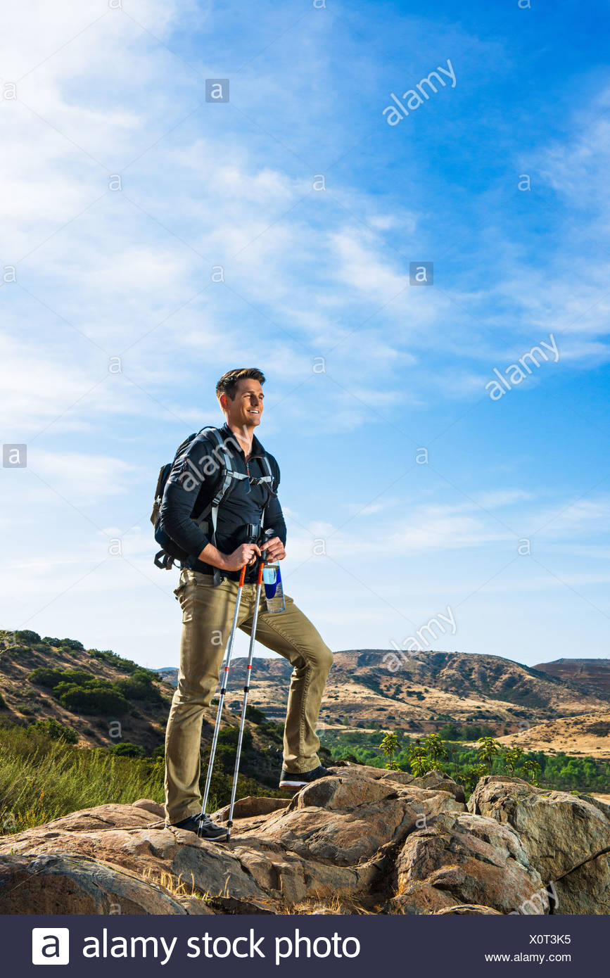 Male hiker on rock - Stock Image