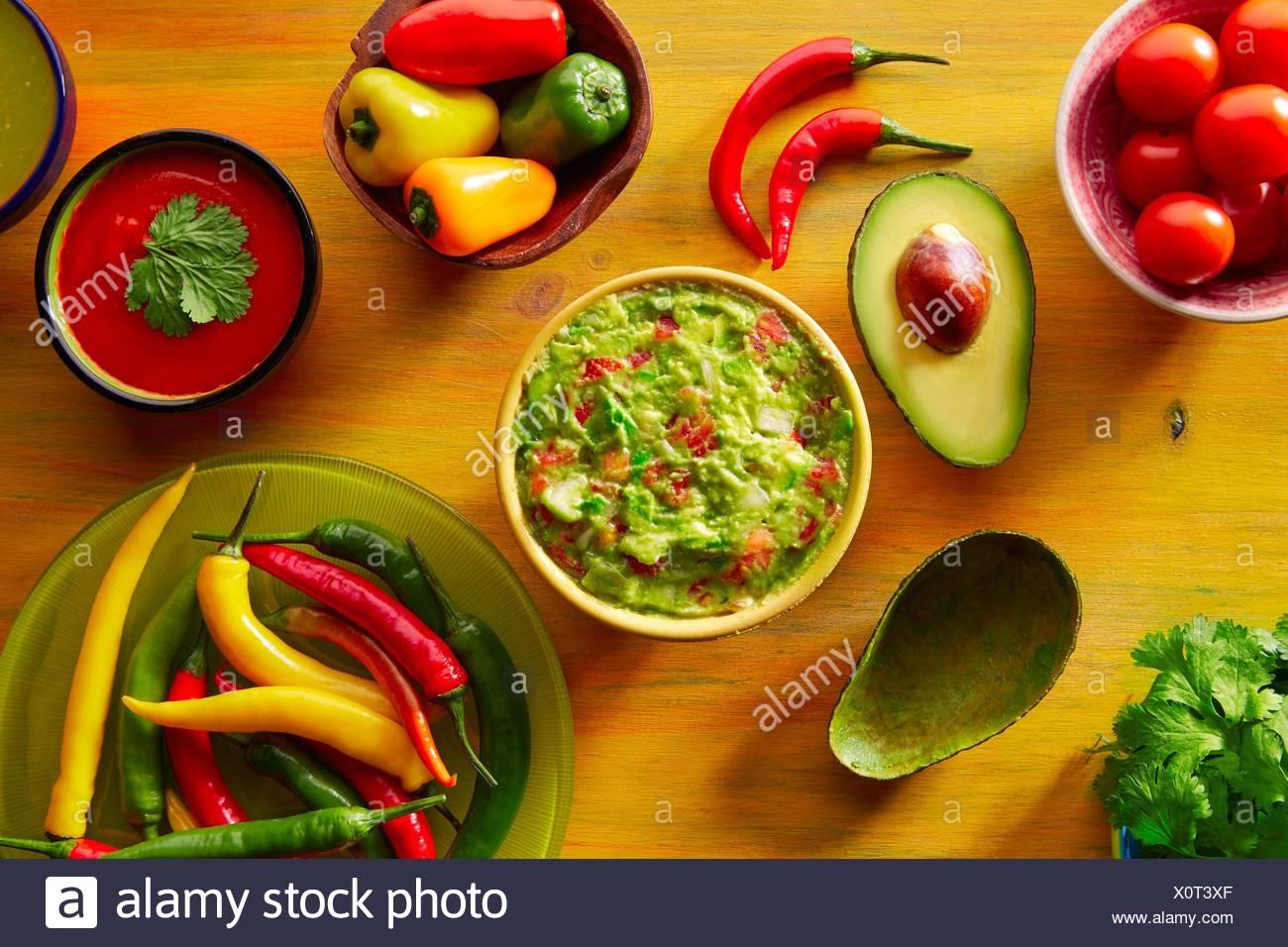 Mexican food mixed guacamole nachos chili sauce dipping cheddar cheese lemon pico de gallo. - Stock Image
