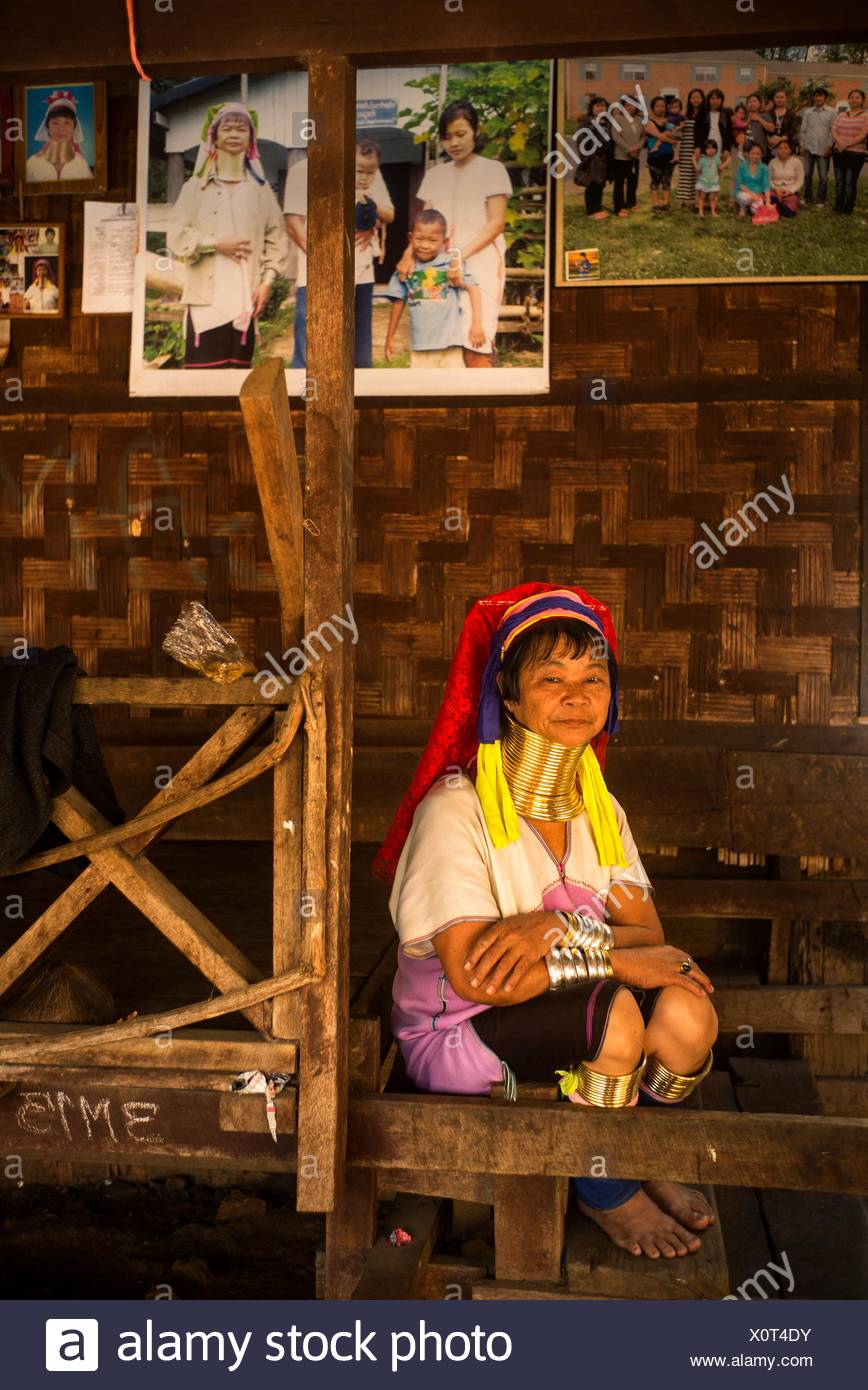 A Karenni woman in front of some pictures sent by relatives who emigrated to the United States. - Stock Image