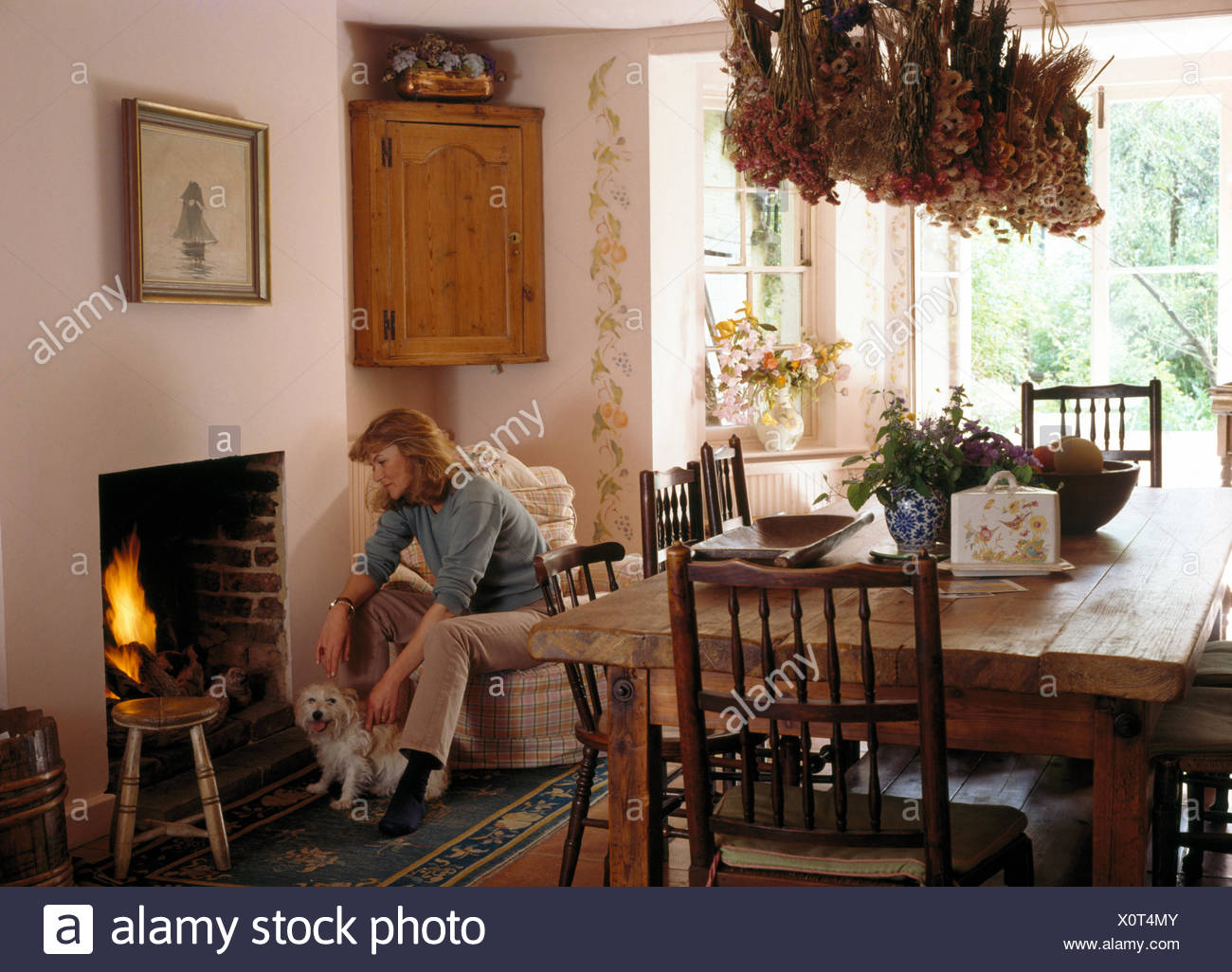 Woman Sitting With A Small Dog Beside Dining Room Fireplace