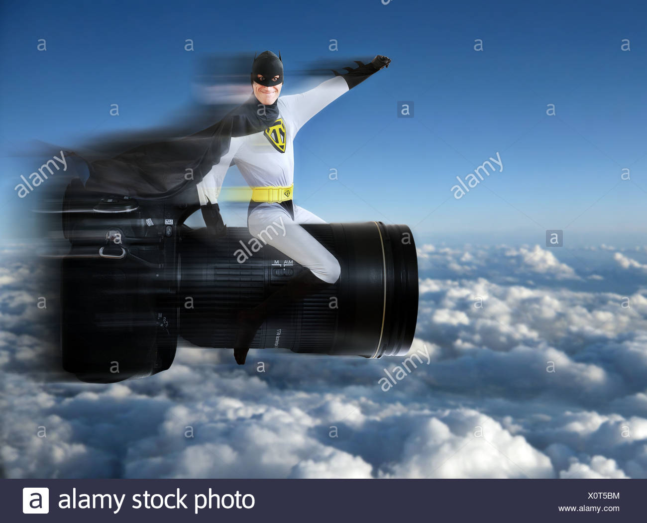 Super hero sitting on a camera and flying over the clouds - Stock Image