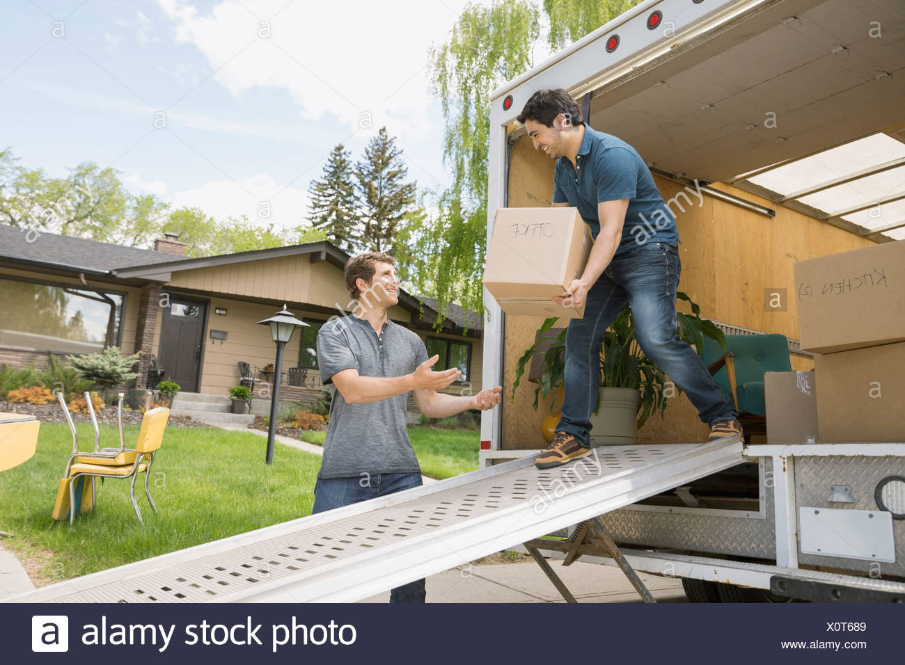Men unloading boxes from moving van - Stock Image