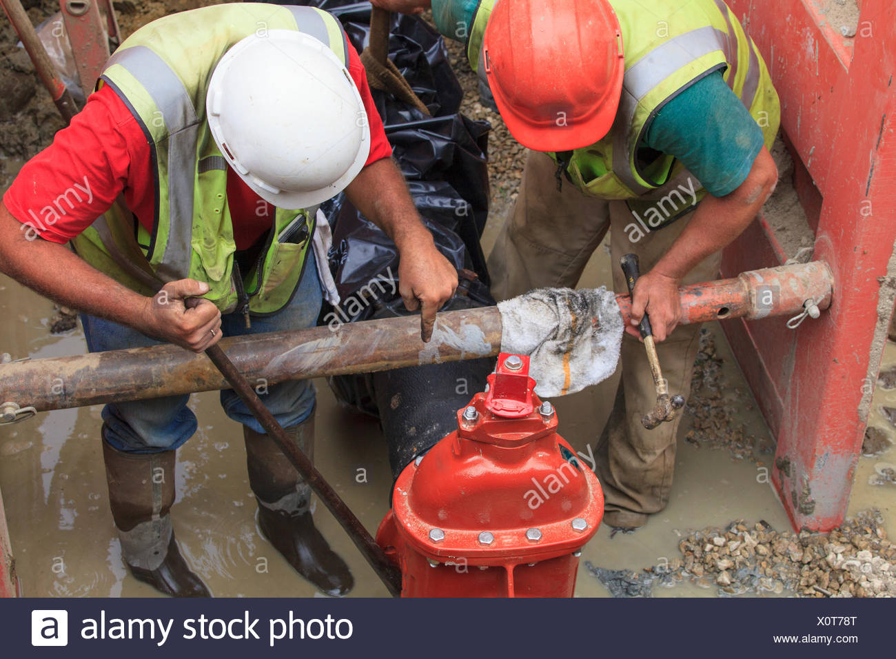 Construction workers adjusting gate valve position on water main - Stock Image