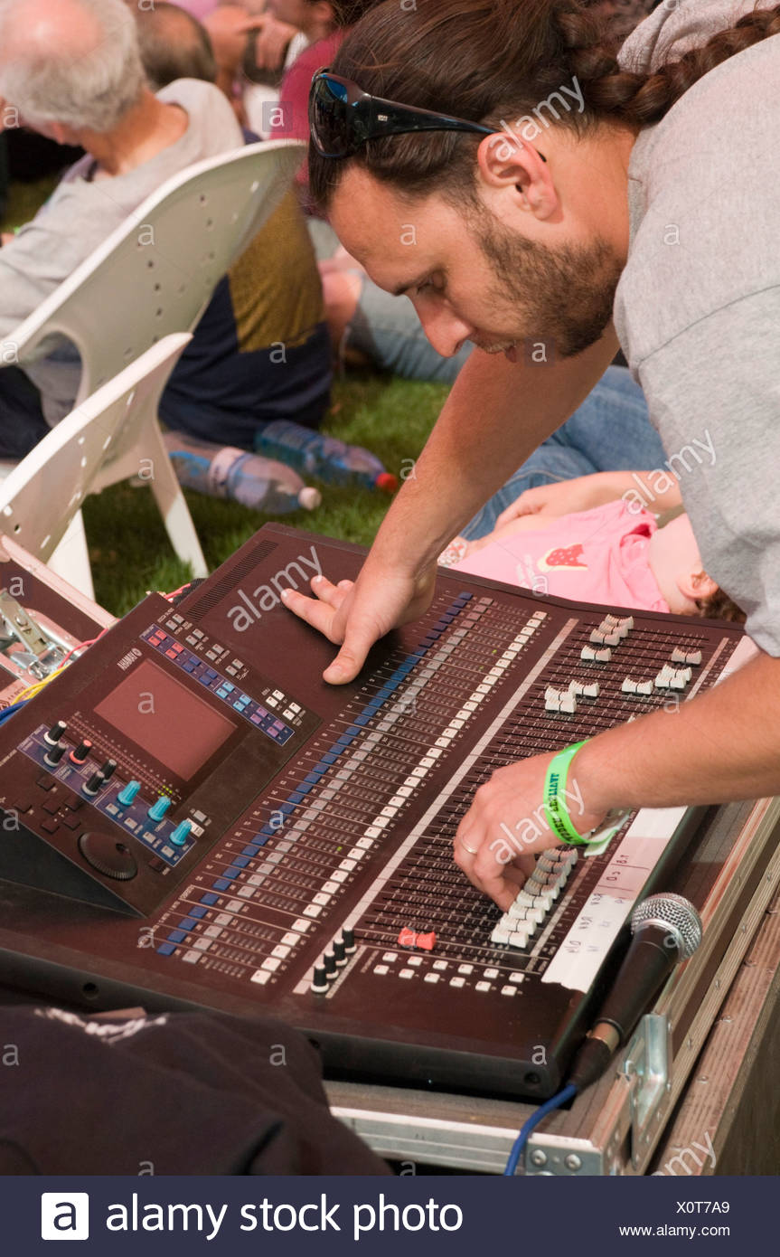 Sound technician at his station during a music performance - Stock Image