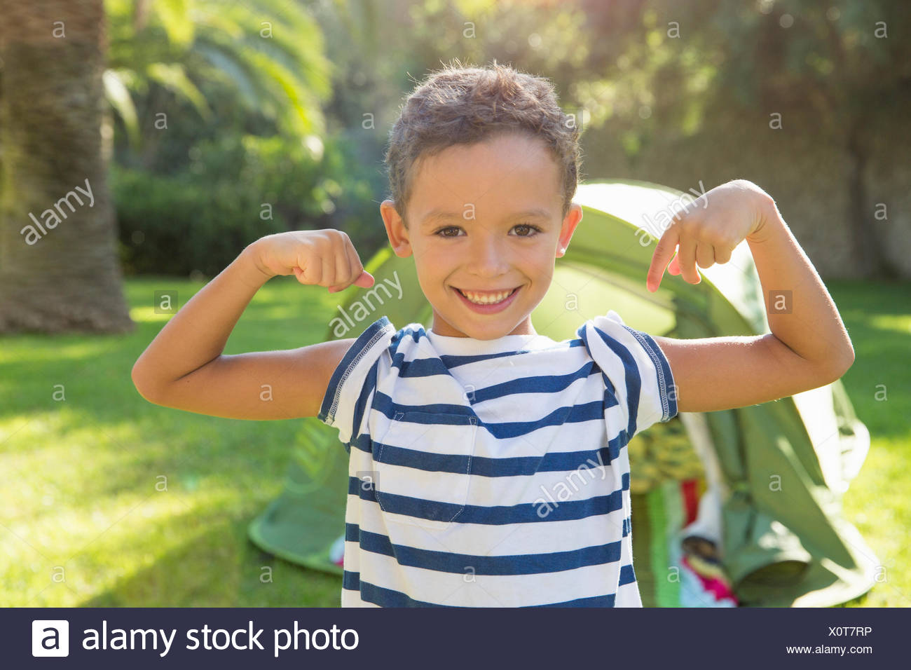 Portrait of boy in garden flexing muscles - Stock Image