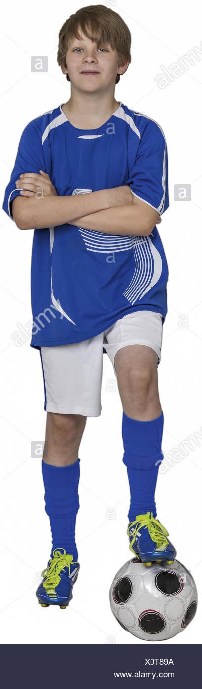 Junge steht mit einem Bein auf Fussball, verschraenkte Arme (model-released) - Stock Image