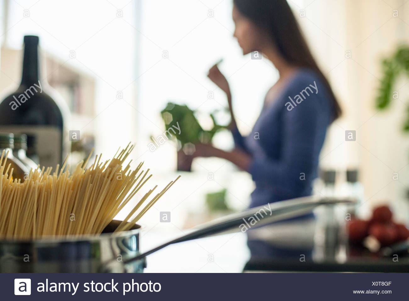 Blurred image of young woman preparing food in kitchen - Stock Image