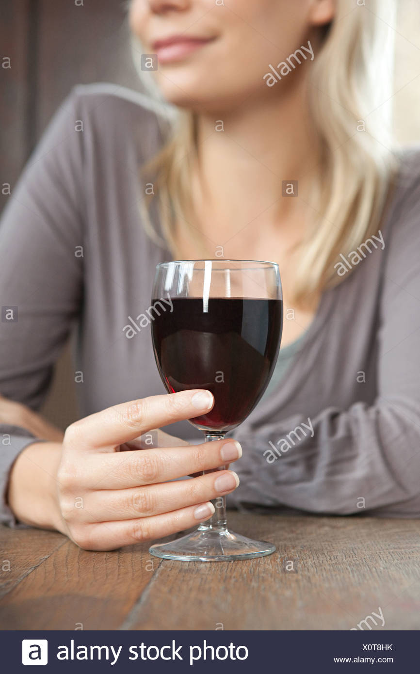 Young woman with red wine in bar - Stock Image