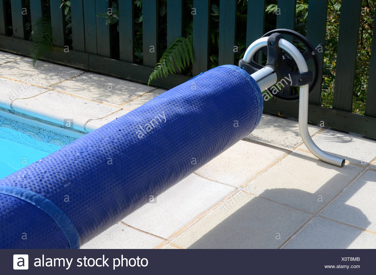 Swimming pool cover on its roller at the end of the pool Stock Photo ...