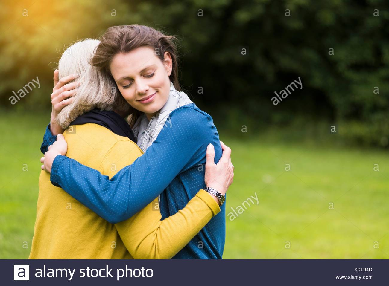 Senior woman and daughter hugging tenderly in park - Stock Image