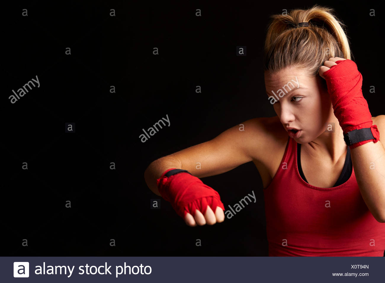 Young blonde woman shadow boxing with arm bent in defence - Stock Image