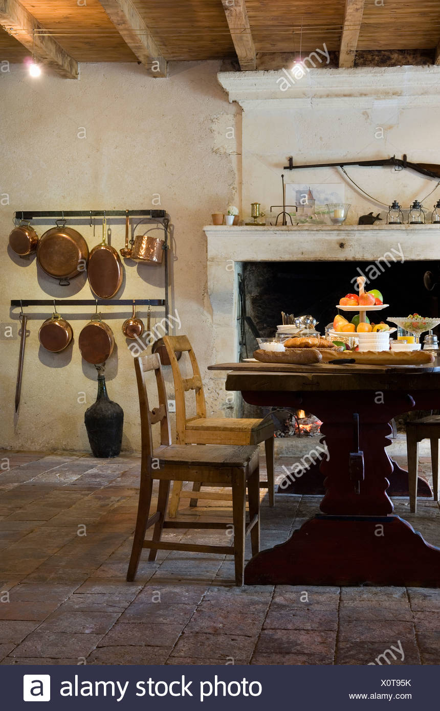 Old wooden chairs at wooden table in French country kitchen ...