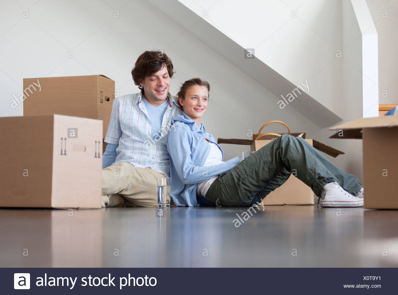Couple sitting with cardboard boxes - Stock Image