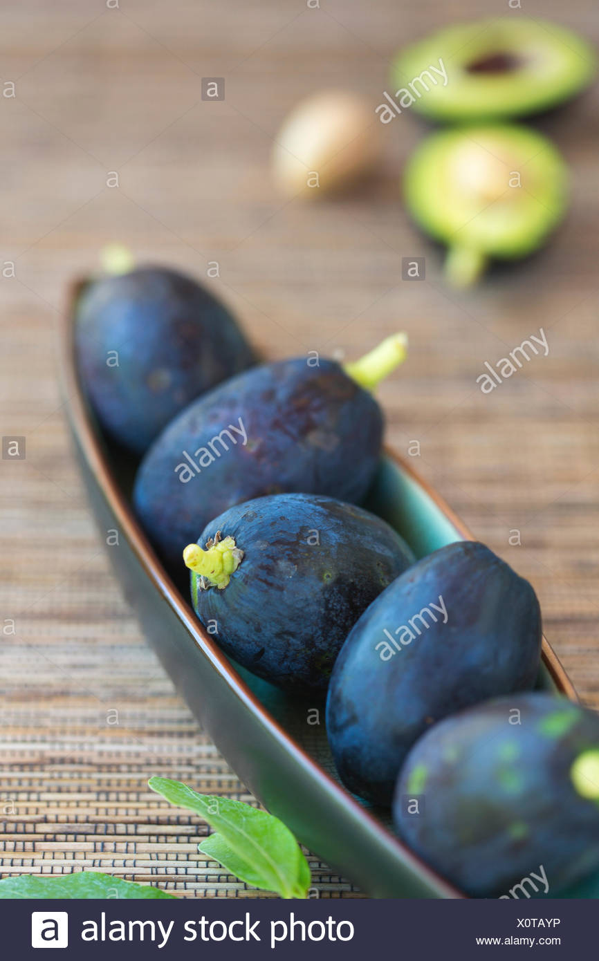 avocado fruits in ceramic dish on woven mat - Stock Image