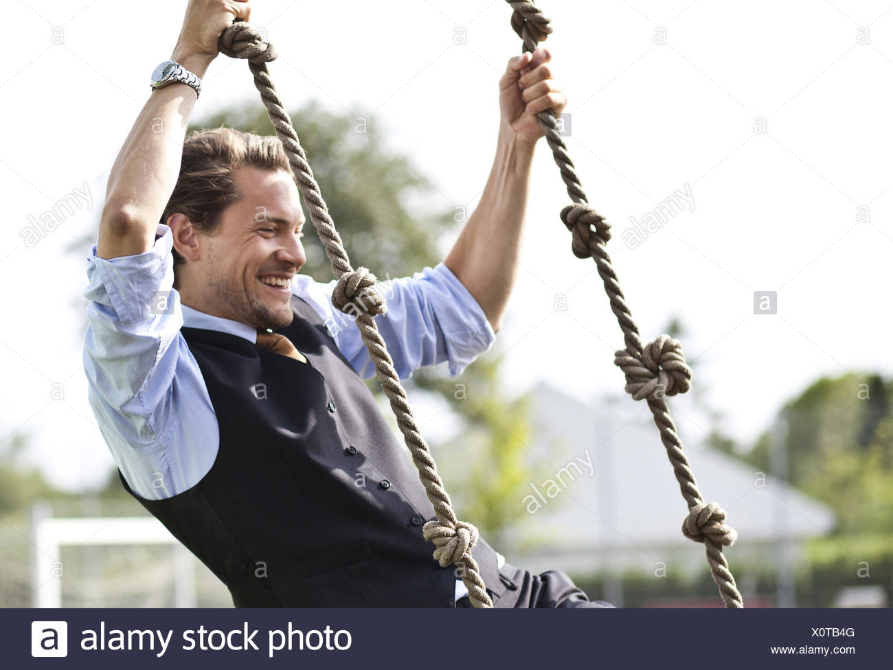 Happy businessman playing, swinging in ropes Stock Photo