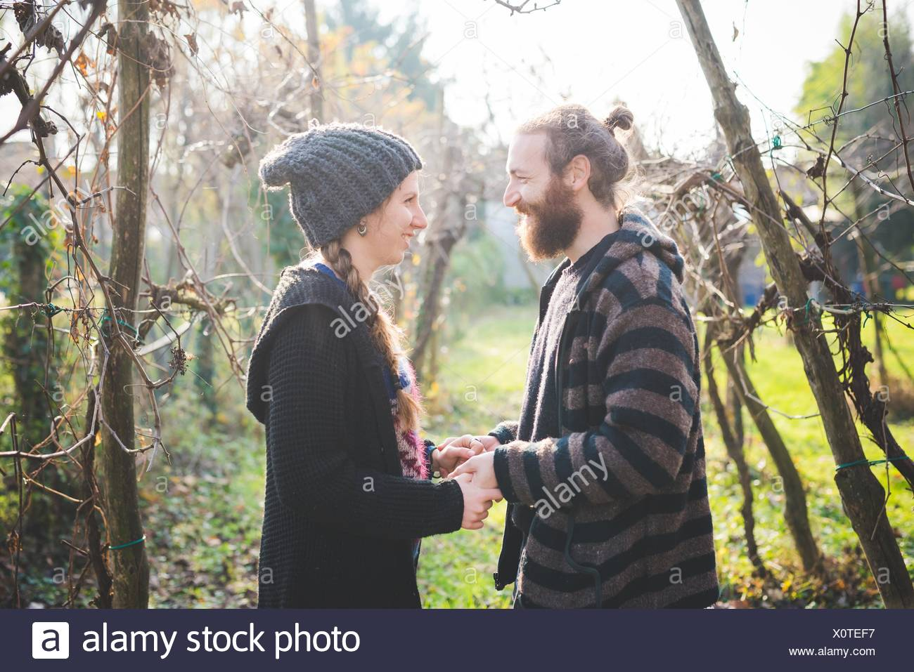Side view of couple among trees face to face, holding hands, smiling - Stock Image