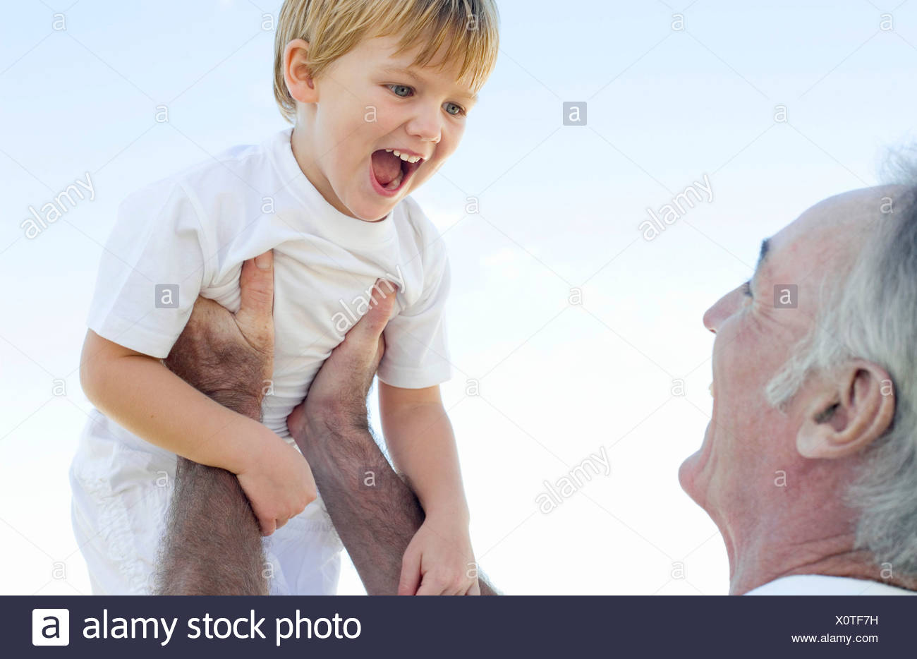 Grandfather lifting his grandson - Stock Image