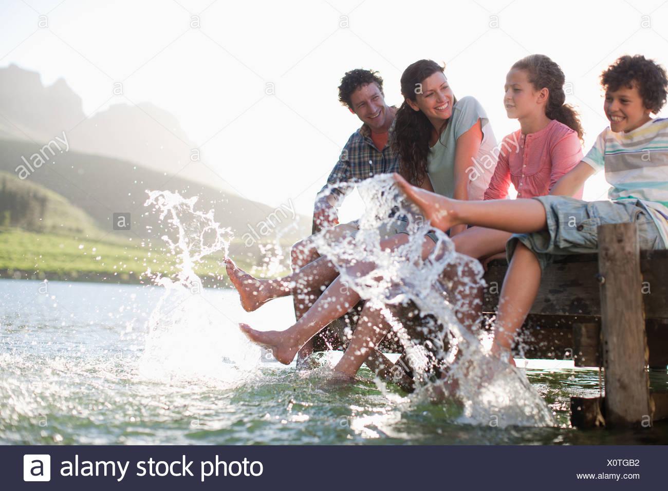 Family on dock splashing feet in lake - Stock Image