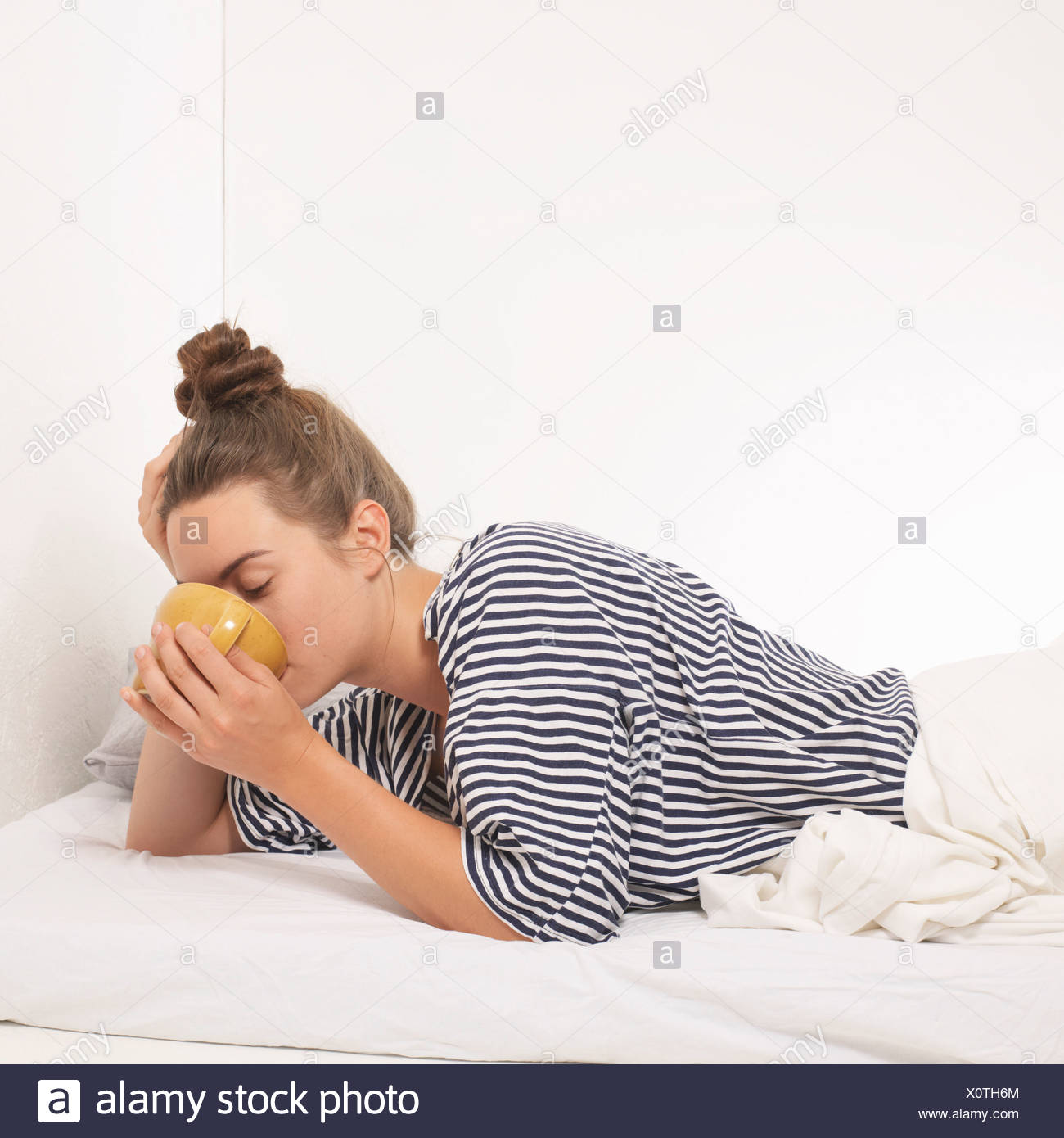 Woman in bed drinking from mug Stock Photo