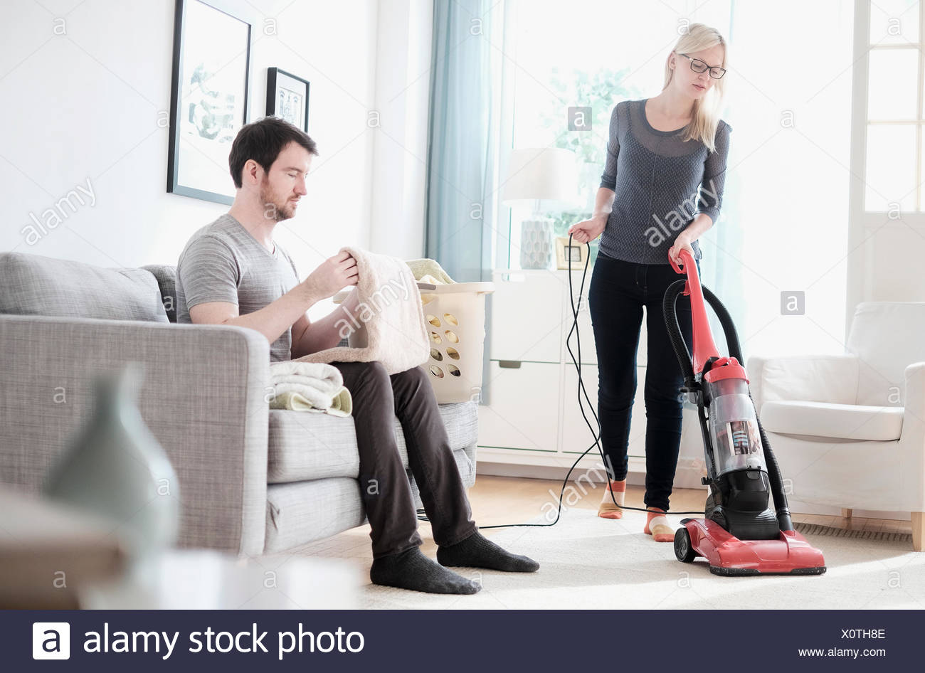 Couple cleaning living room - Stock Image
