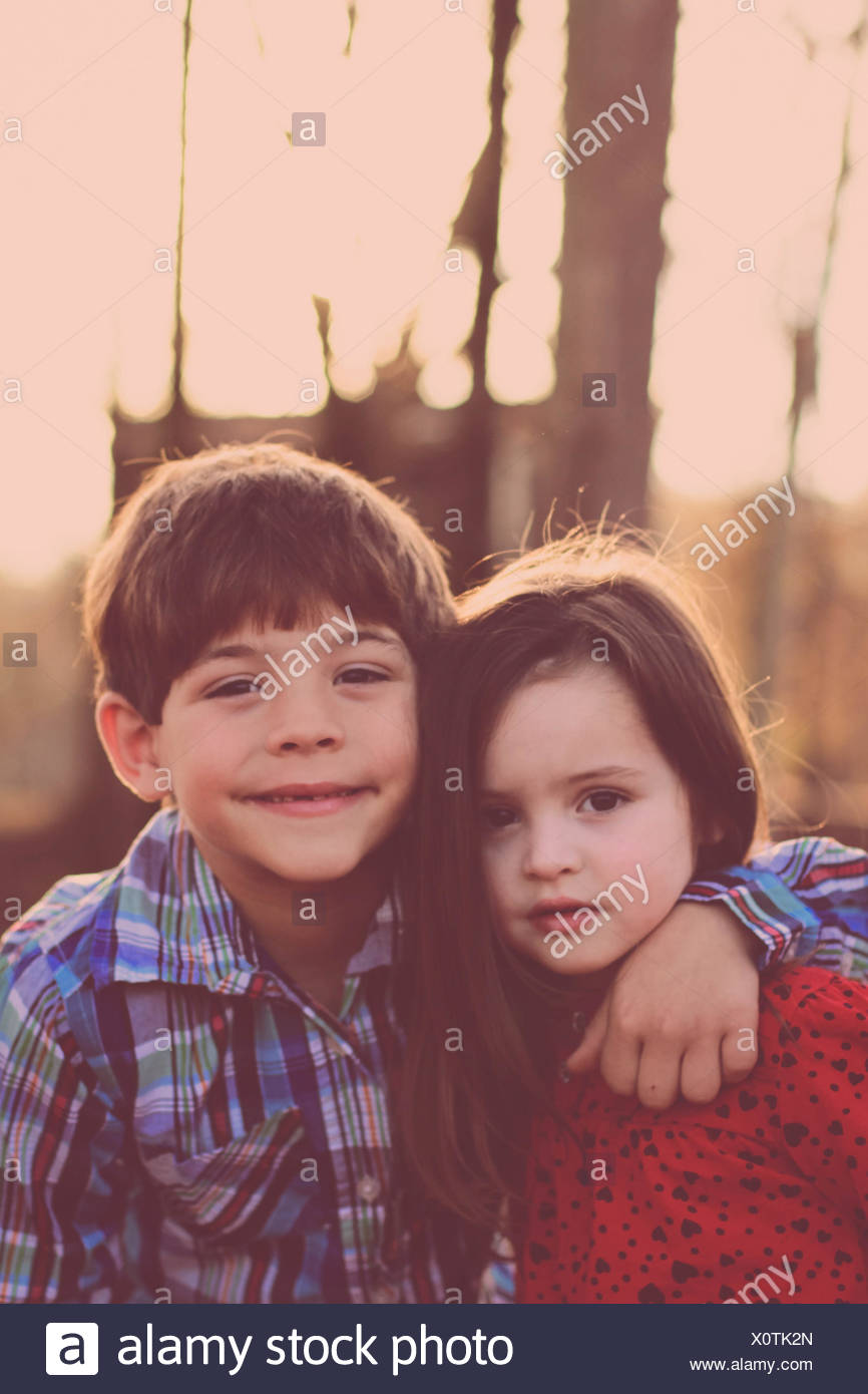 Portrait of sister and brother (2-3, 6-7) in park - Stock Image