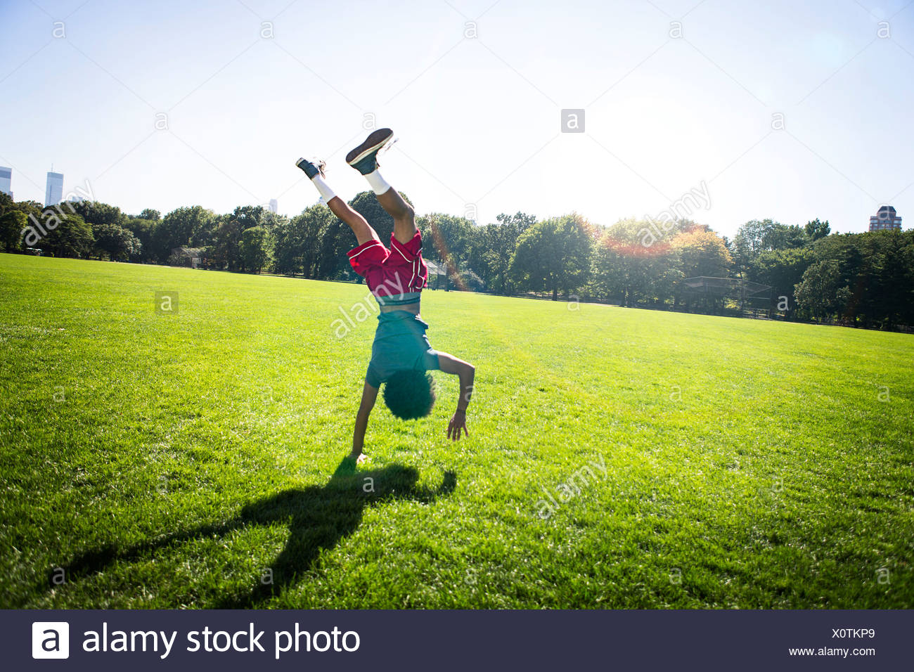 Young man doing cartwheel in park - Stock Image