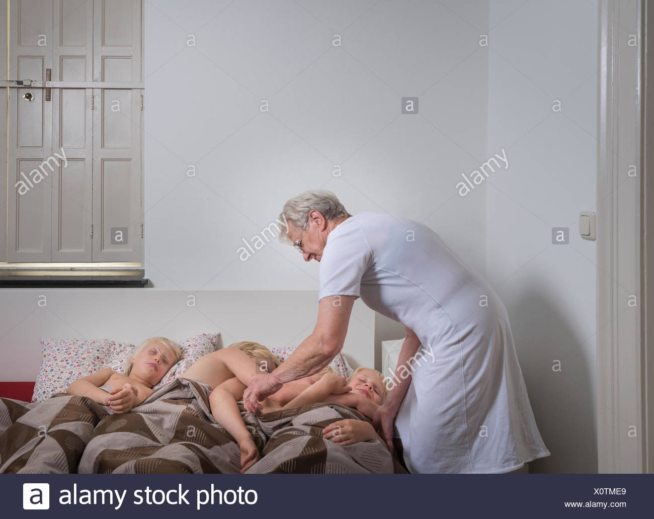Grandmother settling grandsons in bed - Stock Image