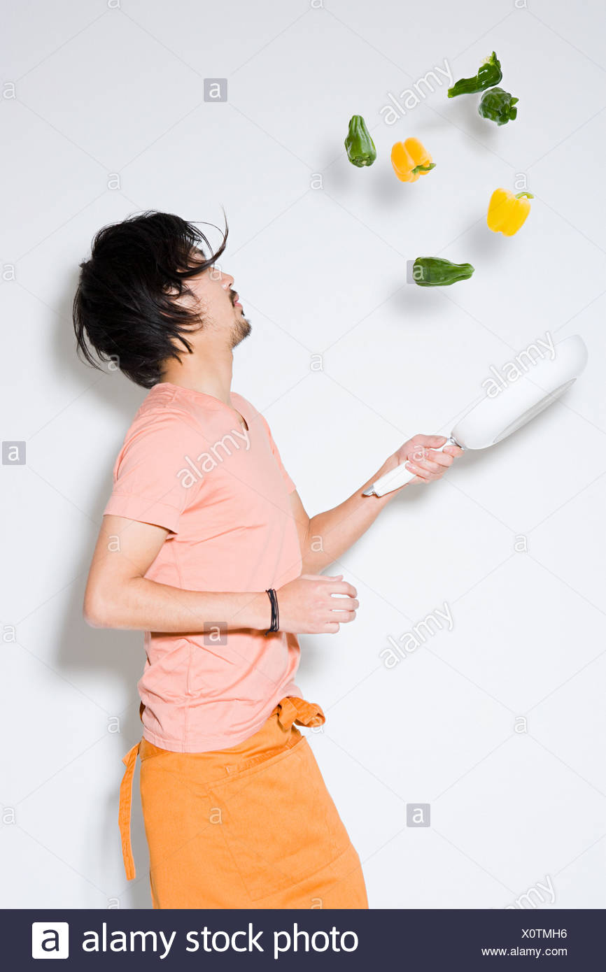 Man tossing peppers - Stock Image