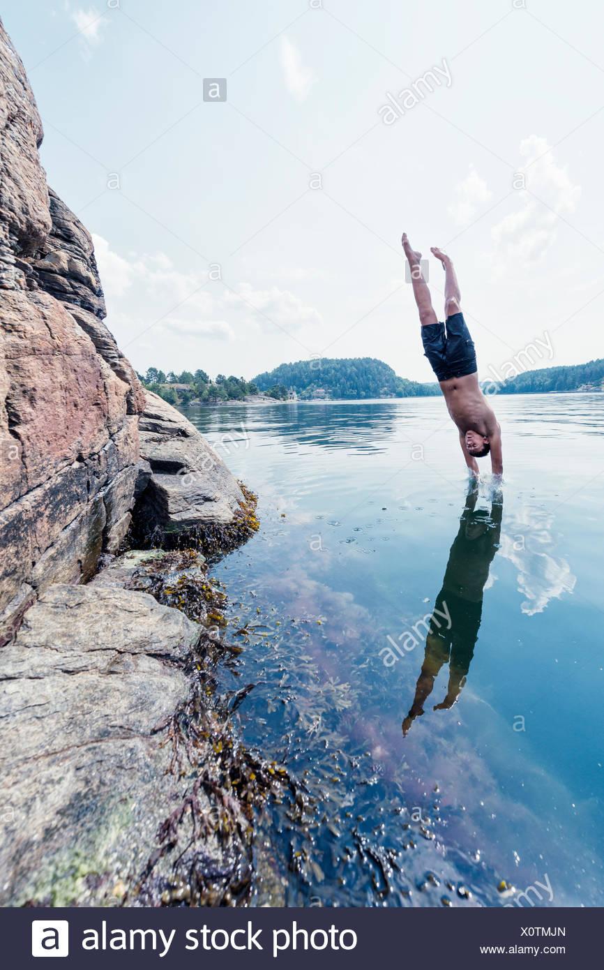 Man jumping into sea Stock Photo