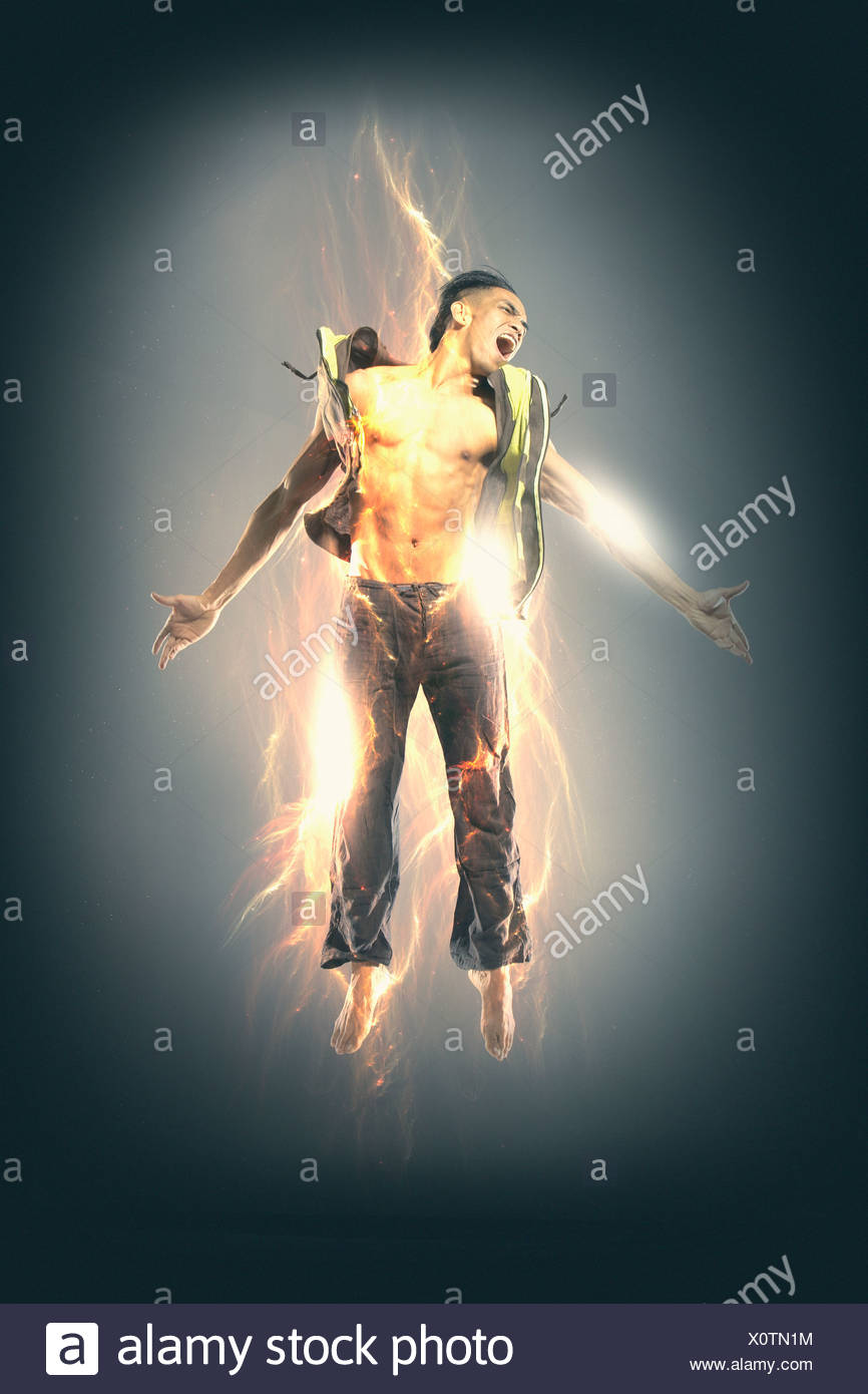 Excited man glowing with electricity - Stock Image
