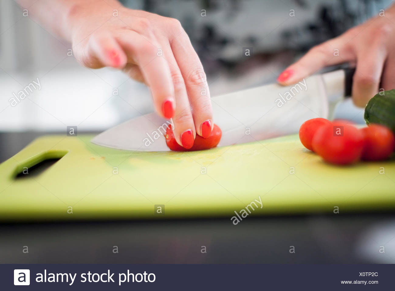 Woman cutting tomatoes on cutting board - Stock Image