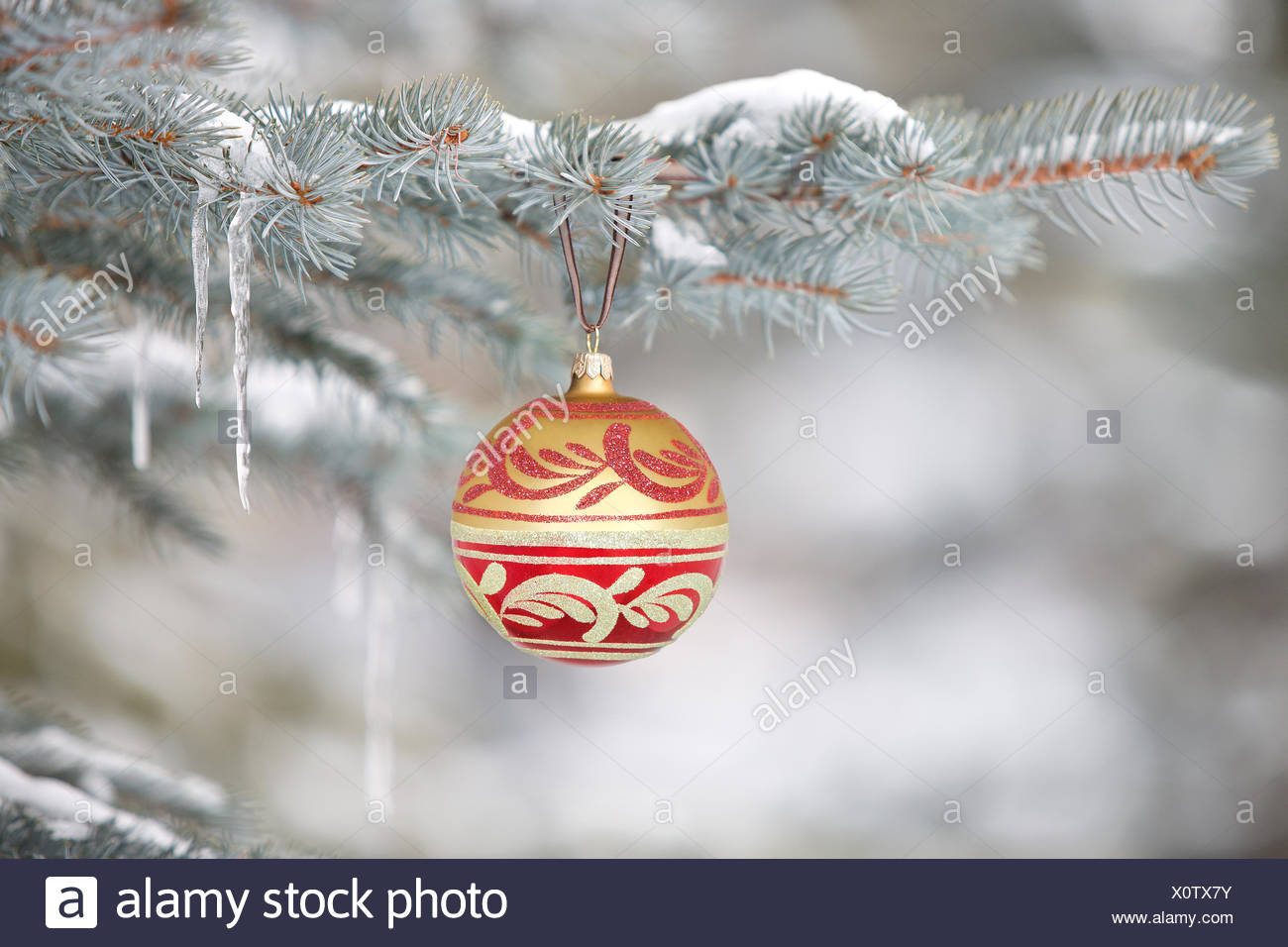 Christmas ornament hanging on tree with icicles - Stock Image