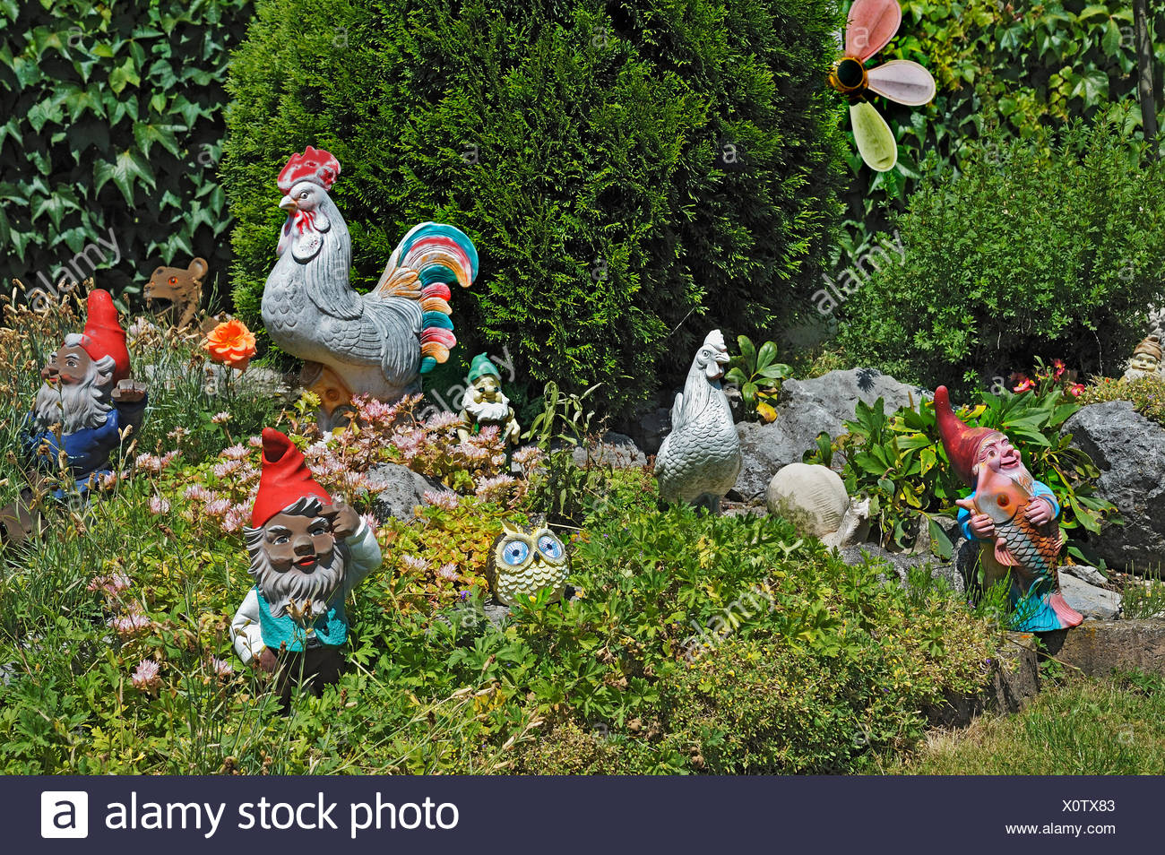 Clay figures, garden gnomes and clay chickens in a garden, Bavaria, Germany - Stock Image