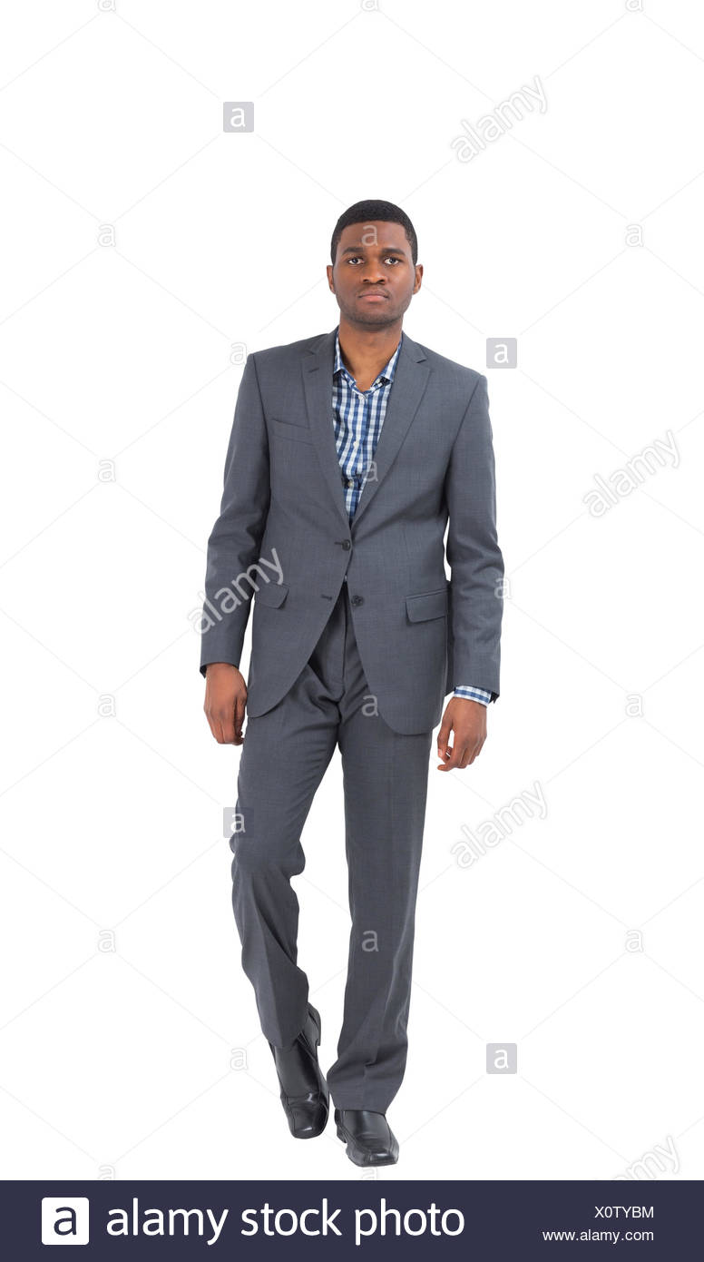 Serious businessman stepping ahead - Stock Image