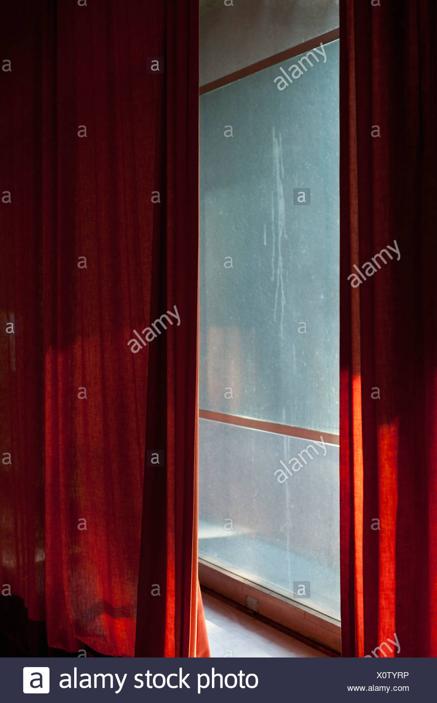 Red Curtains draped in front of dirty window - Stock Image