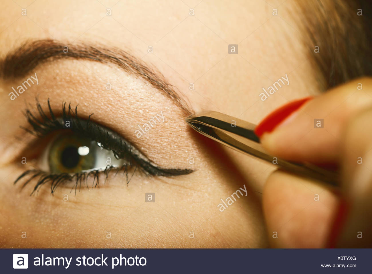 part of face woman plucking eyebrows - Stock Image