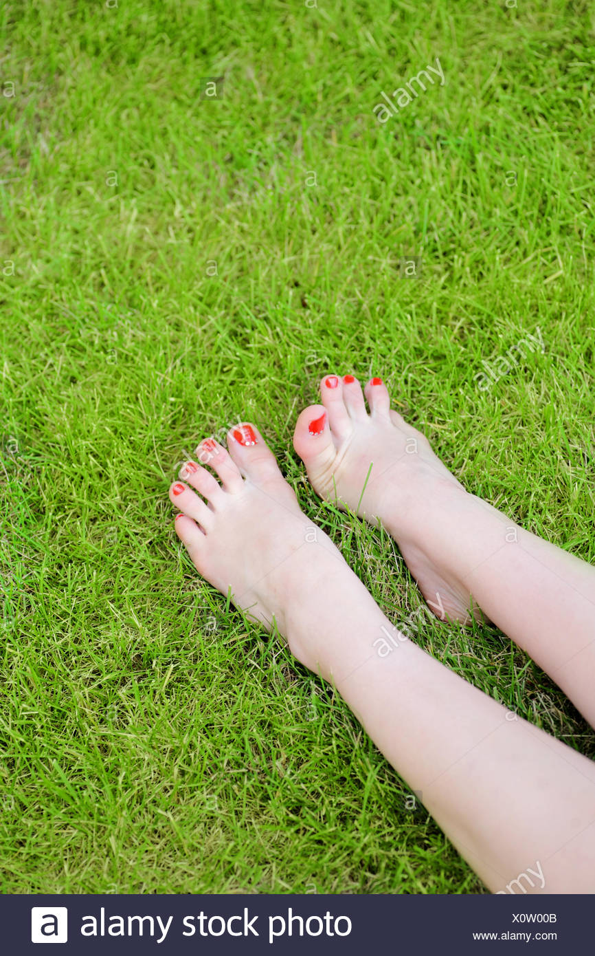 Woman's bare feet in green grass - Stock Image