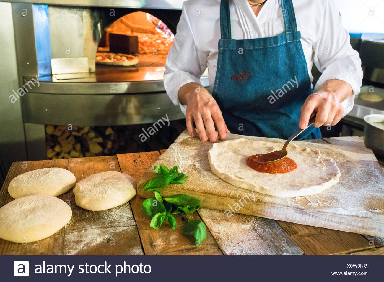 The chef fills the pizza with tomato sauce and fresh ingredients then ready to be cooked in the wood oven Italy - Stock Image