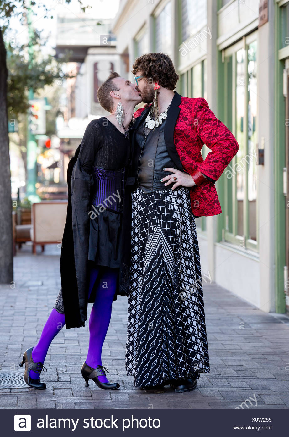 Dramatic Young Gender Fluid Men Kissing - Stock Image
