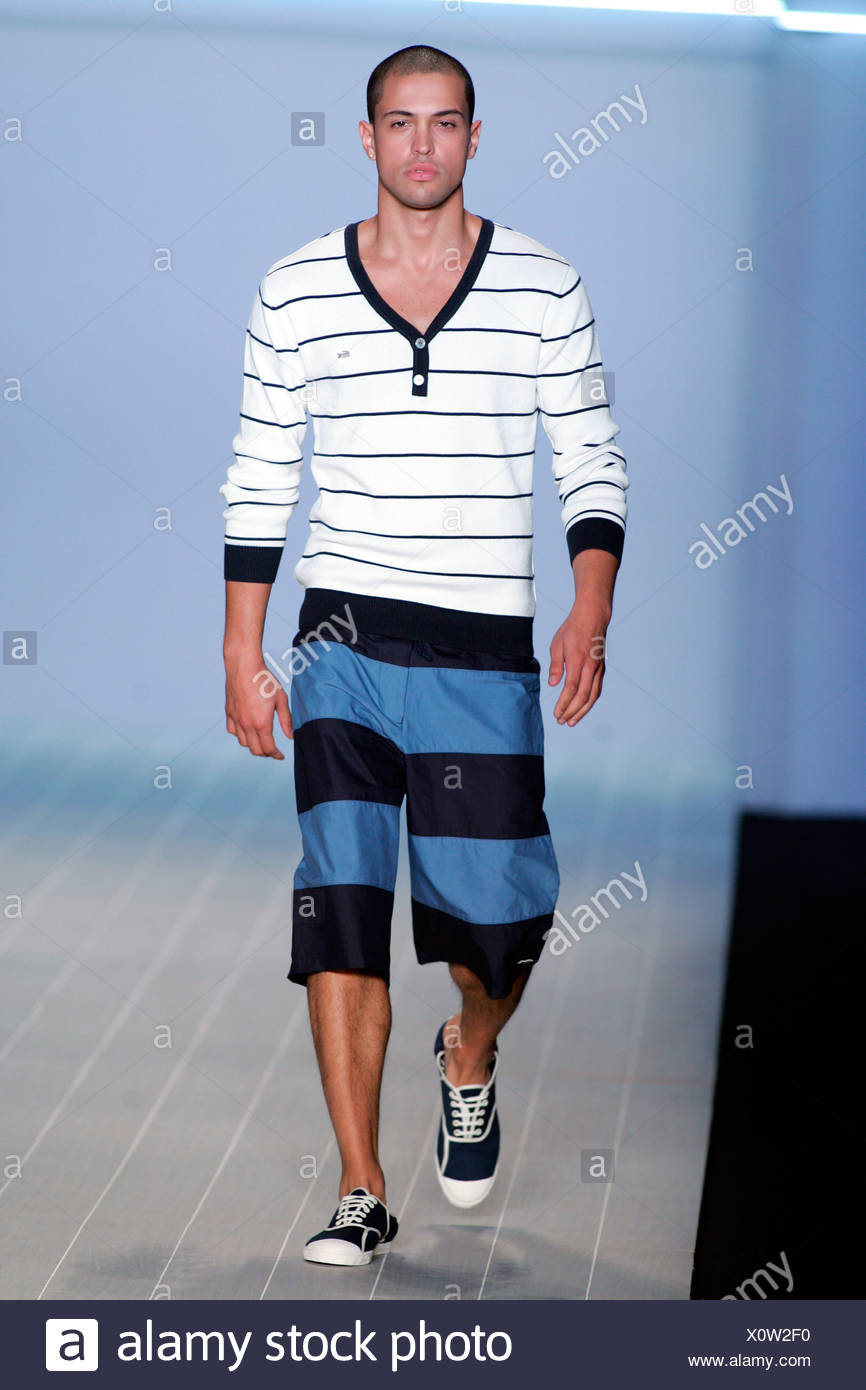 720d9bf062f9 Brunette male model wearing a black and white striped V neck t shirt black  and blue