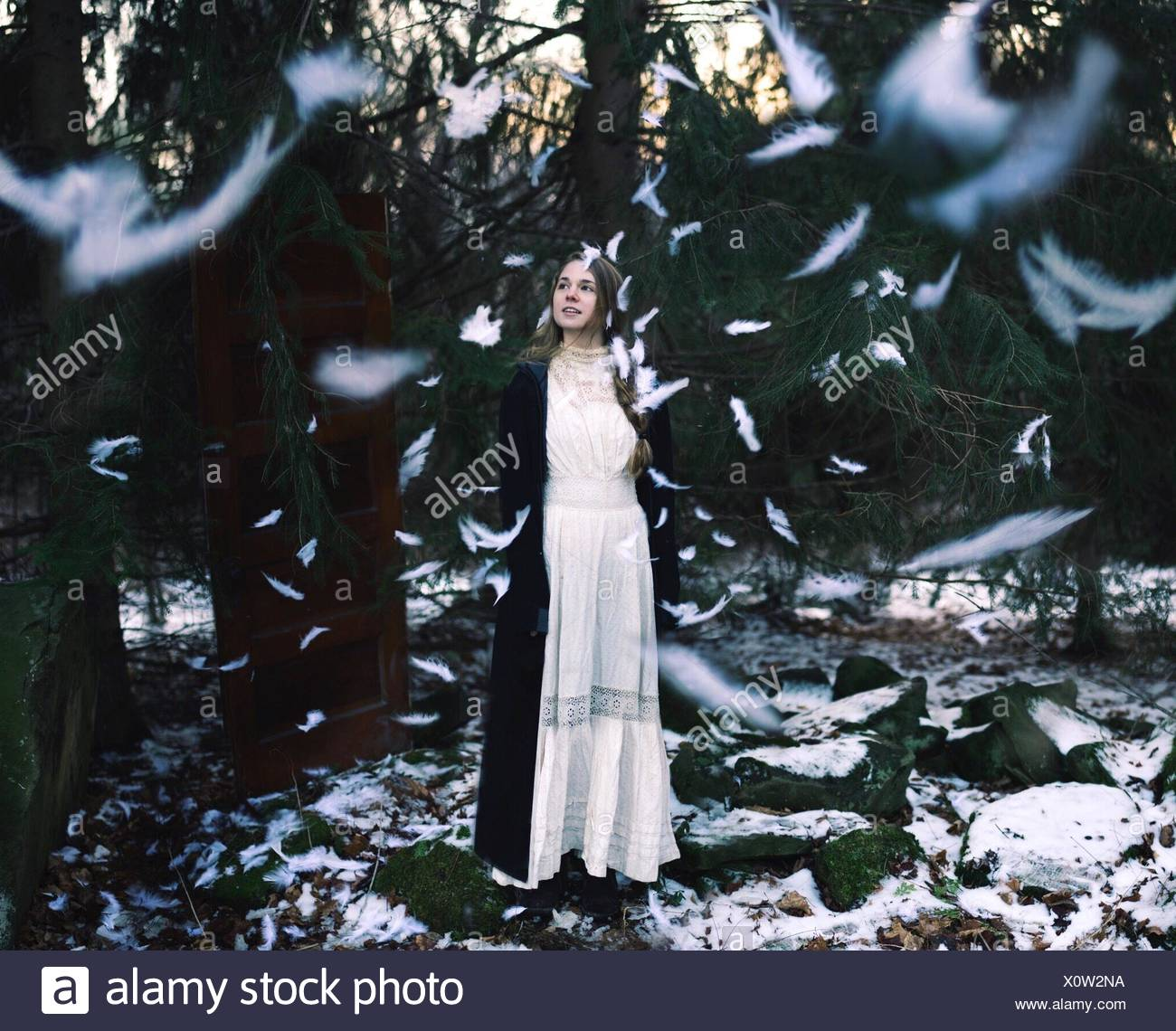 Young woman standing in forest with feathers falling all around - Stock Image