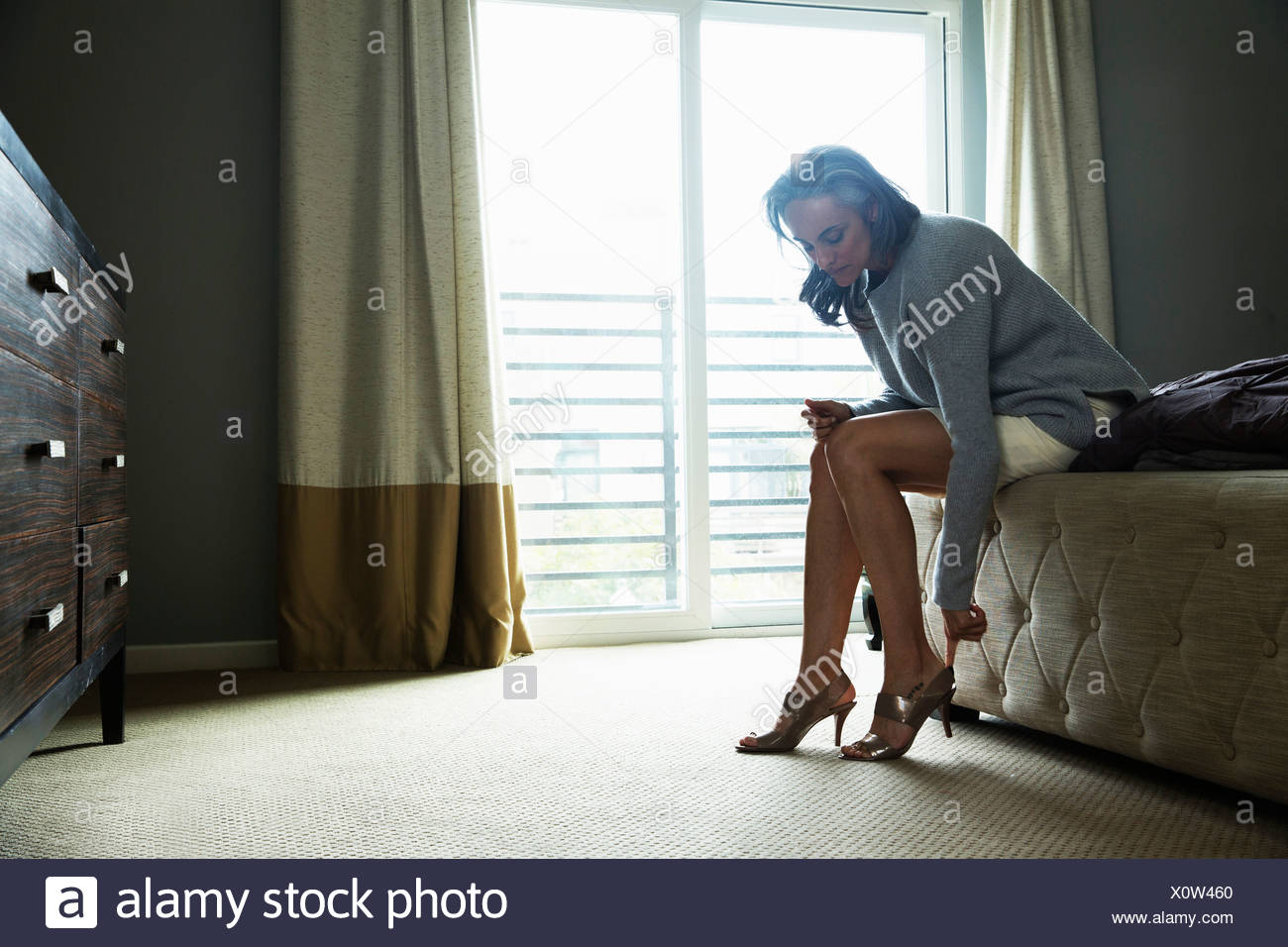 Mature woman sitting on bed putting on high heels - Stock Image