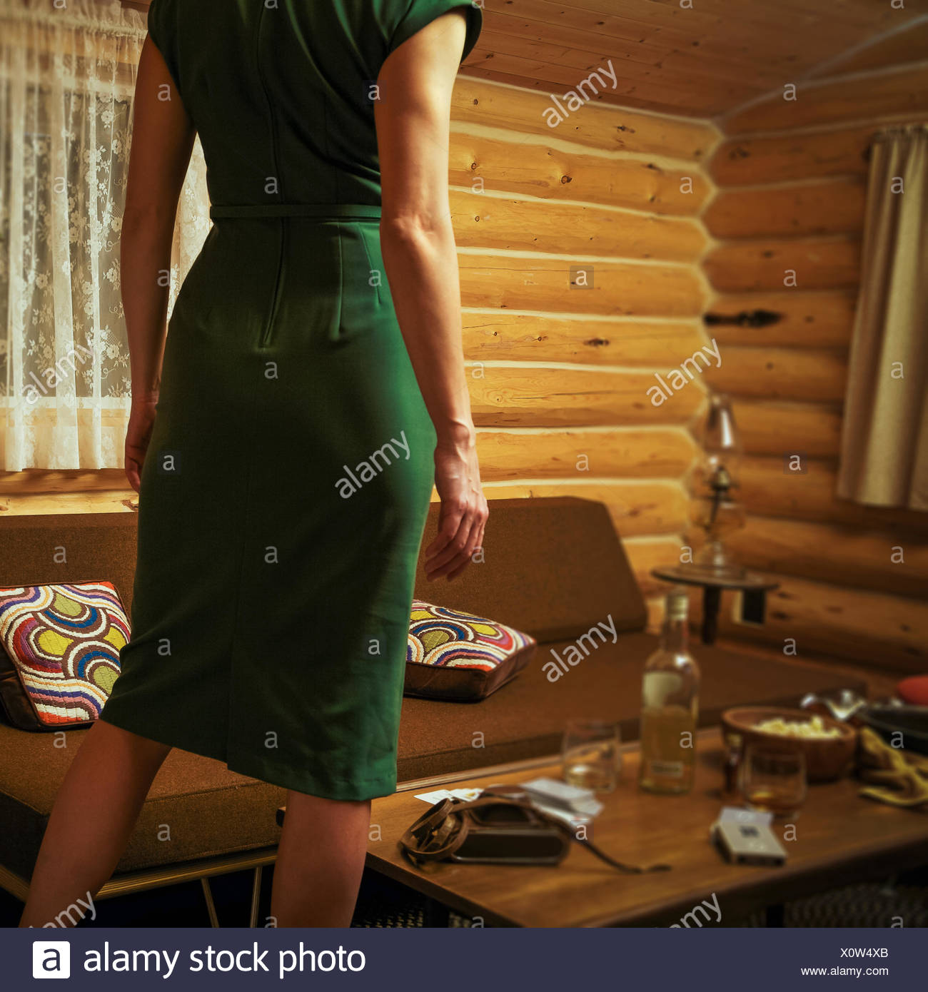 Canada, Alberta, Cochrane, Rear view of woman in mid-century styled log cabin wearing retro dress Stock Photo